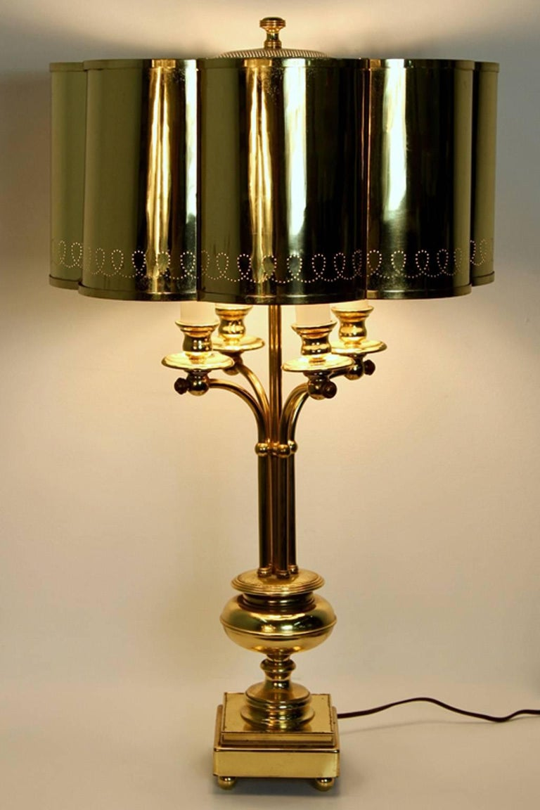 Wonderful Regency modern era table lamp in solid brass. Featuring a lobed shade, perforated decoration, and four sockets. In the manner of Finnish designer Paavo Tynell.