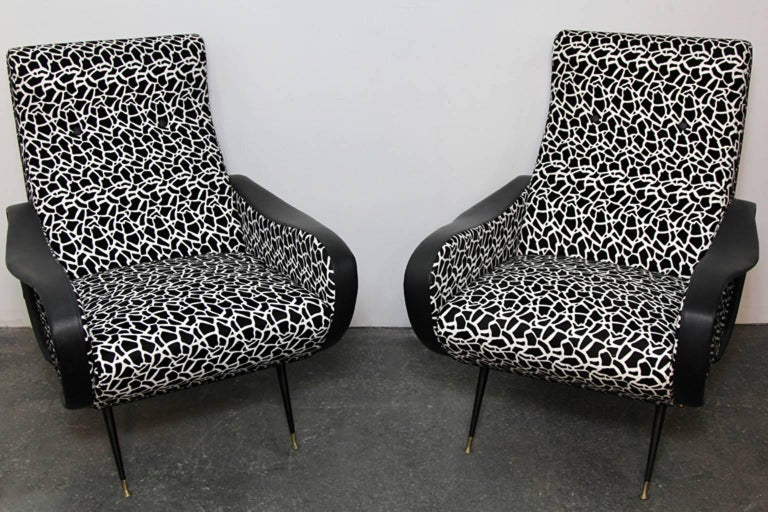 Contemporary exampled of Italian style Mid-Century Modern club chairs. Black and white funky fabric with leather arm details. Some scrapes and tears to leather on arms. Enameled steel legs with brass detail.
