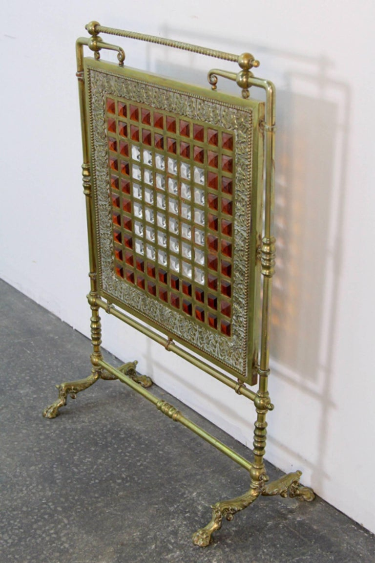 Unique 1900s antique brass fire screen with beveled leaded glass center panel surrounded by finely detailed carving. Exquisite on its own and even more so when backlit by the fire.