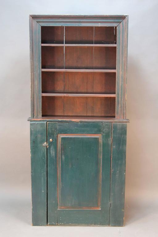 Primitive stepback cupboard with elegant trim. Original red milk paint, blue green painted addend in late 1800s. Solid wood construction with square nails and wood pegs. Made of pine.