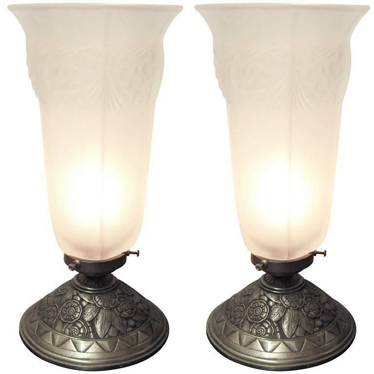French Art Deco table lamp in frosted art glass with a satin nickled bronze base attributed to Sabino. The flanged cylindrical ambient shade with a stylized pine cone and needle decoration is mounted on a floral and leaf motif decorative base.