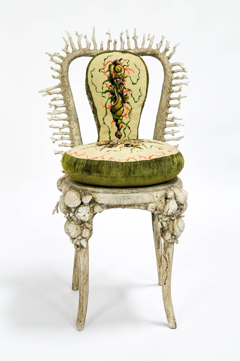 This extraordinary chair is encrusted with real shells and coral, and integrated with seamlessly with resin and paint. Its custom designed incredibly detailed, needlepoint pillows are perfectly fitted to the chair. The hand-painted finish was done