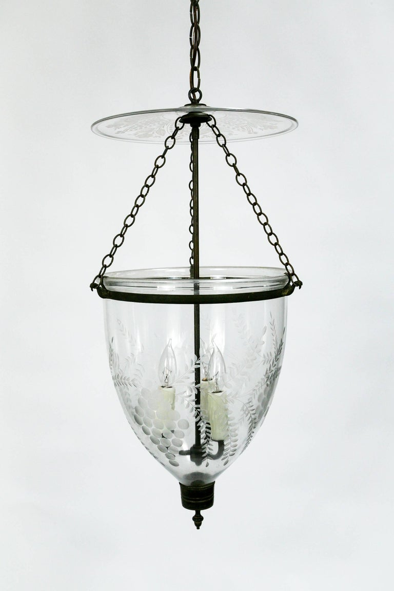 This Georgian style, bell jar pendant lantern is handblown and etched with a lovely, grape and leaf pattern. The etched smoke bell is particularly notable, with an intricate, flower design. The brass glass holder features bird chain hooks. The