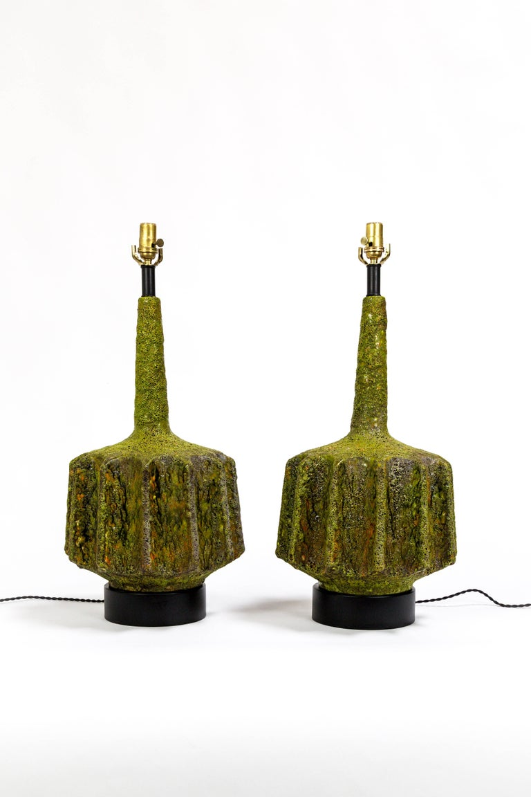 These striking lamps were designed by Marcello Fantoni; a beautiful shape with scalloped sides.  Monumental, fat lava glazed ceramic in multifaceted green with hints of orange and yellow.  Newly wired with black, rayon covered twisted cord.  Italy,