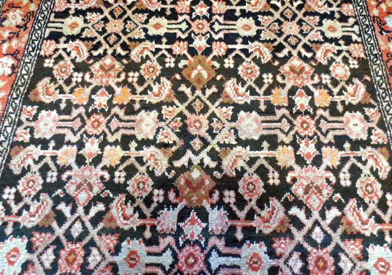 This is an antique Persian Malayer rug, circa 1900s with a lot of flow and movement. A series of complex and beautiful floral and angular patterns lead the viewer down the rug in a lively display of activity. The deep navy blue background only