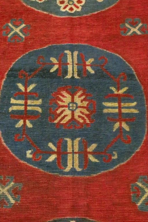 This is an antique Samarkand rug from East Turkistan, circa 1900s. Three circular medallions float on a red field that is surrounded by an infinity border and another outer border. Tones of muted reds, ivories, navys and greys, convey a feeling of
