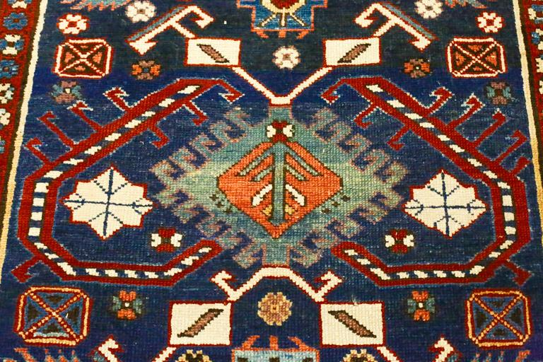 This is an antique Caucasian Kazak runner, circa 1870s. It is in mint condition with bold colors. It features bracketed medallions surrounded by a lively display of angular animals and symbols in dark navy field with accents on red, orange, ivory,