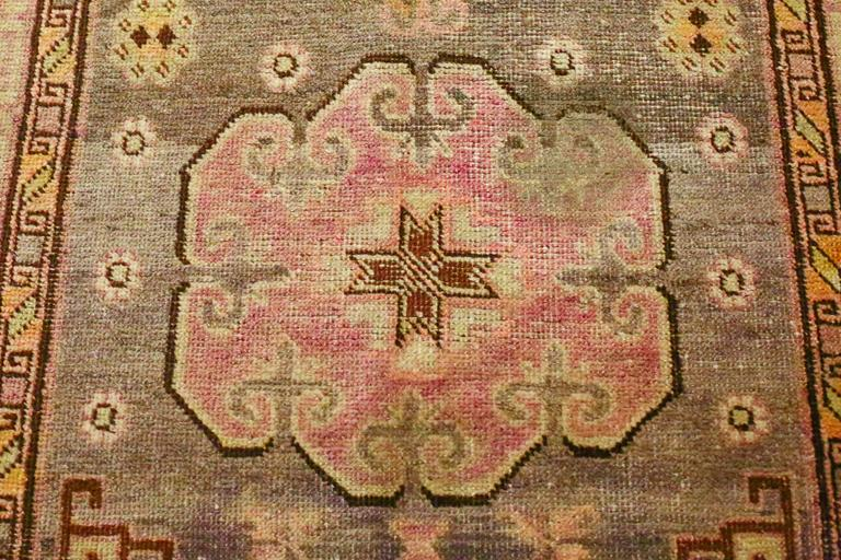 This is an antique Khotan rug from East Turkistan circa 1880s. Three cloud-like central medallions are set against a field of stylized floral forms. Multiple borders frames the field, each with different designs and symbols. Shades of pinks, olives,