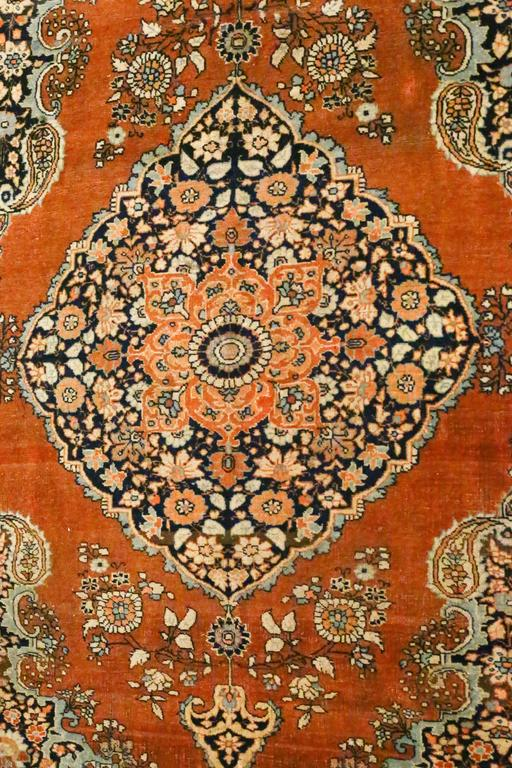 This is an antique Persian Tabriz Haji Jalili rug, circa 1880s. It is beautifully woven and meticulously crafted in rust, greens, blues, yellows, navy colors. Surrounding the large stylized medallion are floral interlocking patterns in varying