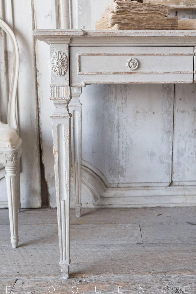 Eloquence® Herra writing desk in Gustavian grey finish. This piece shows off Classic lines adorned with delicate carvings, all finished a soft neutral tone that will compliment any living space. Lovingly worn at the edges and featuring two spacious