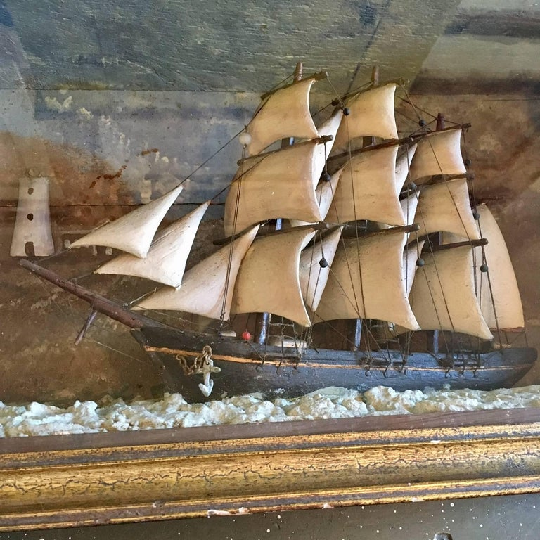 A 19th century nautical shadowbox with hand carved ship in stormy seas on a