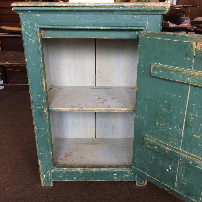 Green single door cupboard with decorative beading. Interior old repaint.