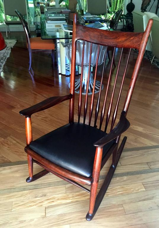 An early model of rocking chair designed and made by Sam Maloof (1916-2009), one of the most esteemed American woodworker who instilled a timeless fluid aesthetic into American modern design. Rarely constructed in rosewood and upholstered in black