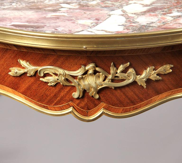A late 19th century Louis XV style gilt bronze-mounted marble-top lamp table.  The shaped circular Breche Violette marble insert top, above a bronze mounted frieze, on tapering bronze mounted legs and scrolled acanthus sabots.