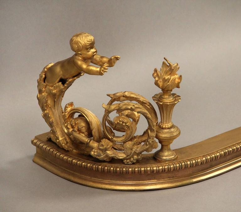 A very fine late 19th century gilt bronze fireplace fender  The centre of the fender with a wreath and scrolling foliage with berries, each end with a child reaching toward a flame for warmth.