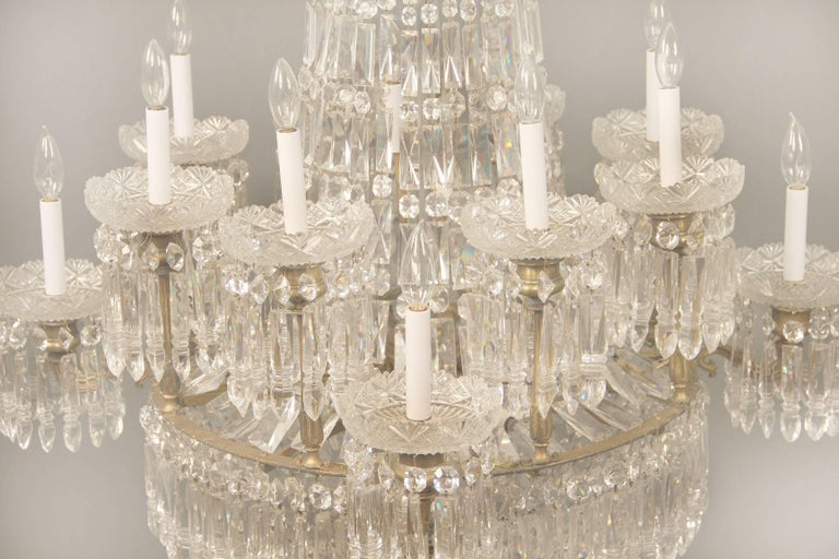 An exceptional early 19th century gilt bronze and Waterford crystal eighteen light chandelier  An etched crown above a crystal string body leading to a beaded basket with drop crystals, each of the twelve tiered perimeter lights with top quality cut