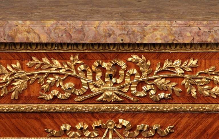 A fantastic late 19th century gilt bronze-mounted Louis XVI style parquetry commode  By Zwiener Jansen Successeur  A marble top above a frieze set with three drawers with pierced laurel decoration, over three garland-hung parquetry cupboard