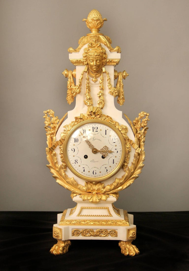 An exceptional late 19th century gilt bronze-mounted marble three-piece clock set  By Ferdinand Gervais  The lyre shaped case surrounded with bronze roses, acanthus and lilys, a large female mask with berried swags adorns the front and back of