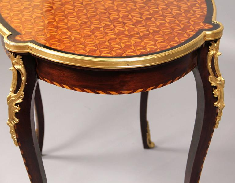 Late 19th century Louis XV style gilt bronze mounted parquetry-top center table.
