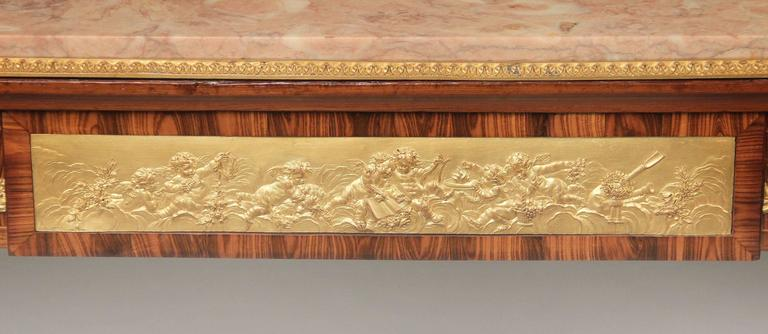 A very fine late 19th century Louis XVI style gilt bronze mounted occasional table.  The rectangular marble top above a frieze drawer centered with a bas-relief plaque cast with music-making putti, with a simulated drawer to the reverse, the sides