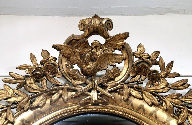 """A fine late 19th century carved giltwood and gesso mirror  Of oval form with dove """"love birds"""" and roses along the top and a sea shell at the base. The entire frame has beautiful inlaid floral etchings. Beveled mirror."""