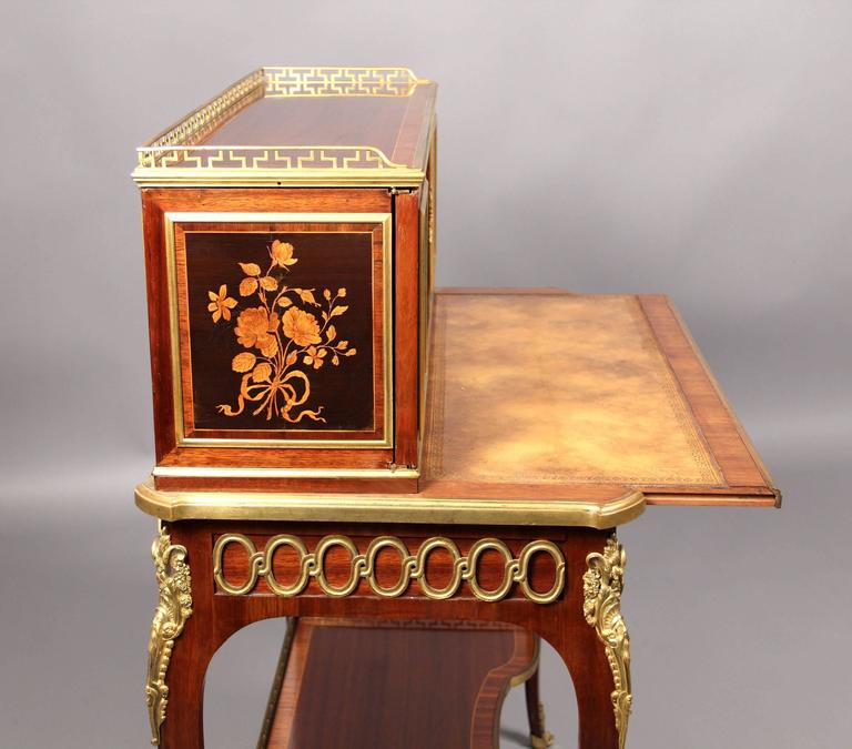A fine mid-19th century Louis XV style gilt bronze-mounted marquetry desk  By Guillaume-Edmond Lexcellent  The upper structure consisting of two doors and a small drawer above a single long drawer, gilt bronze faces on each of the legs, the