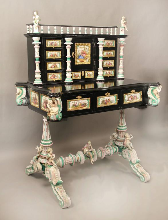 A lovely late 19th century gilt bronze-mounted German K.P.M. porcelain desk  Decorated all-over with porcelain plaques painted with scenes of courting couples, the upper section with a central cupboard door mounted with a square plaque and nine