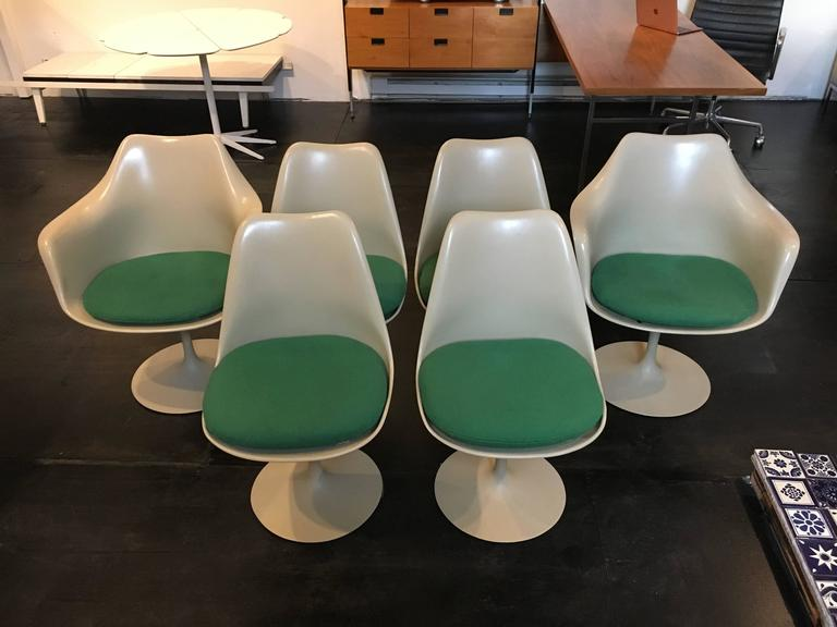 Set of six Eero Saarinen designed tulip chairs manufactured by Knoll. Set includes two armchairs and four side chairs. All chairs have swivel bases and original Knoll cushions.