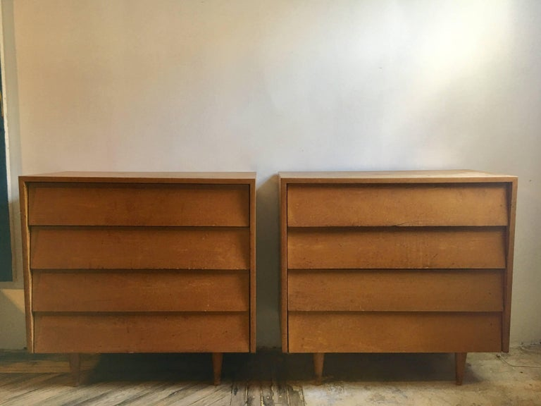 A pair of maple dressers designed by Florence Knoll, featuring slant front drawers, set on tapered feet.