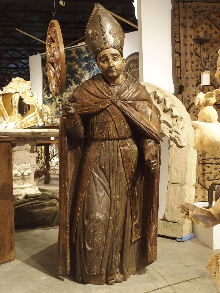 This 64 inch high antique statue of a Bishop dates to circa 1650 and is German in origin. Starting in the 15th and 16th centuries, there was a large demand for ecclesiastical carvings throughout central and western Europe. Large statues were