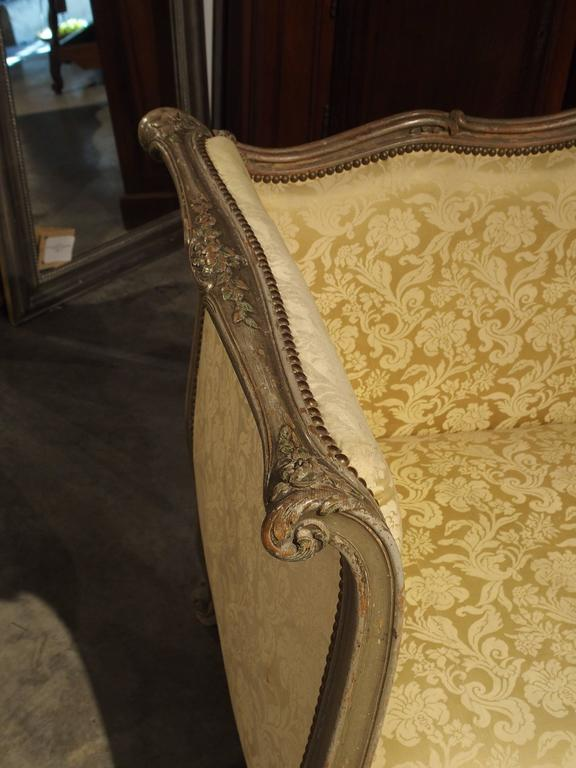 This antique, parcel-paint Louis XV style canapé or settee has a graceful, central domed, shaped back. The scrolled side arms are full height allowing the person to rest their back with full support, if choosing to lounge on the settee. There are