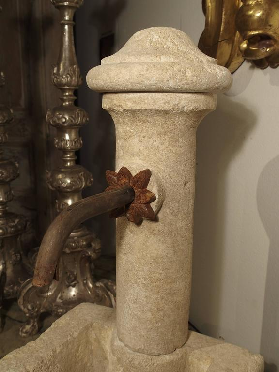 This unusual and charming French tabletop or small garden fountain has been hand-carved in Provence, from Estaillade stone. The fountain has a round columnar back where the spout is. A decorative iron foliate motif surrounds the opening for the