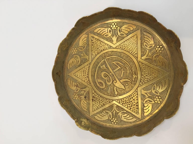 Pair of small round brass Persian metal trays or keys holders change tray, vide poche. Decorative handcrafted round brass dishes with six pointed stars and Arabic writing hand-hammered with floral designs and geometric Moorish designs. Great brass