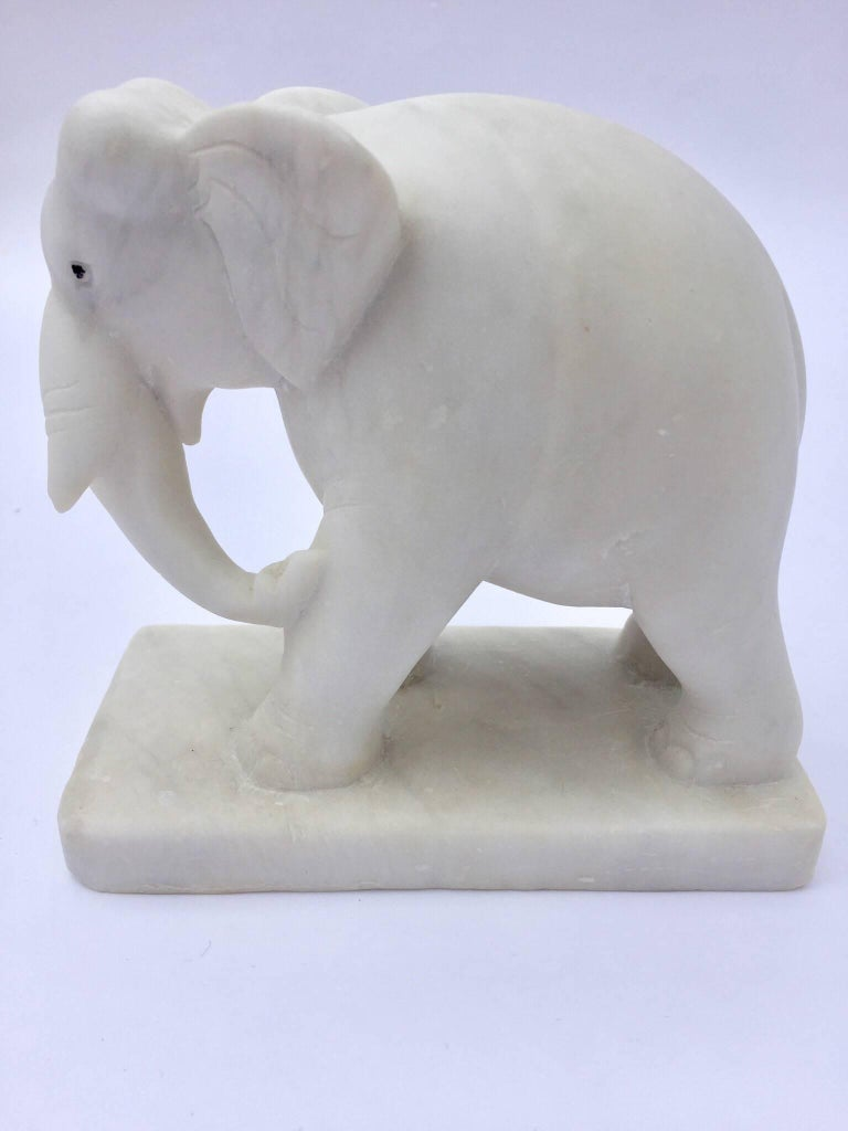 Elegant sculpture that show an elephant carved in white marble presented on a stand.