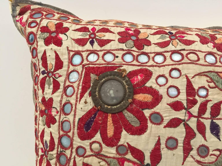 19th century, Rajasthani colorful embroidery textile made into a decorative throw pillow. Handcrafted with floral pattern embroidered with silk thread and embellished with small metal mirrors depicting flowers in bloom and birds. In shade of red,