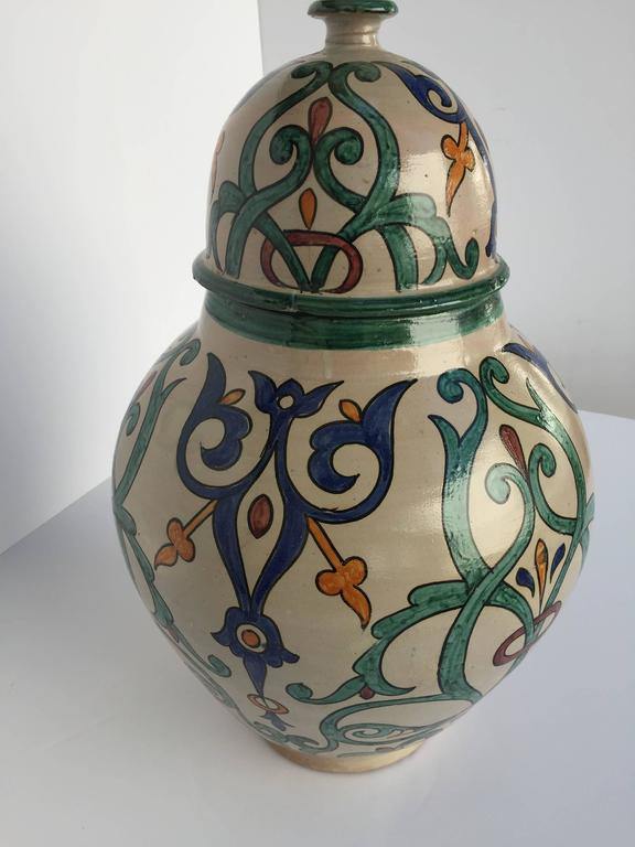 Large Moroccan glazed ceramic urn with lid from Fez.  Granada style ceramic handcrafted and hand-painted with Moorish foliate designs in blue, teal, Safran and red colors on ivory background. A pair is available price is for 1. Large size: 25 in.