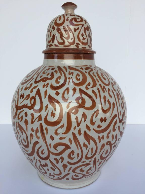 Large Moroccan glazed ceramic urn with lid from Fez.  Moorish style ceramic handcrafted and hand-painted with Arabic calligraphy writing. This kind of Art Writing looks calligraphic is called Lettrism, it is a form of art that uses letters that are