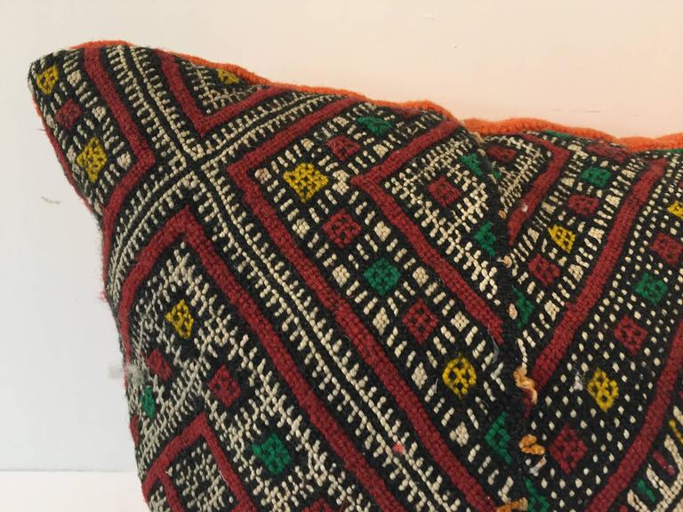 Moroccan Berber handwoven tribal throw pillow made from a vintage rug. The front and the back are made from a different rug, front is more elaborate and back is more plain. Geometric African tribal designs in red, white and black and some green