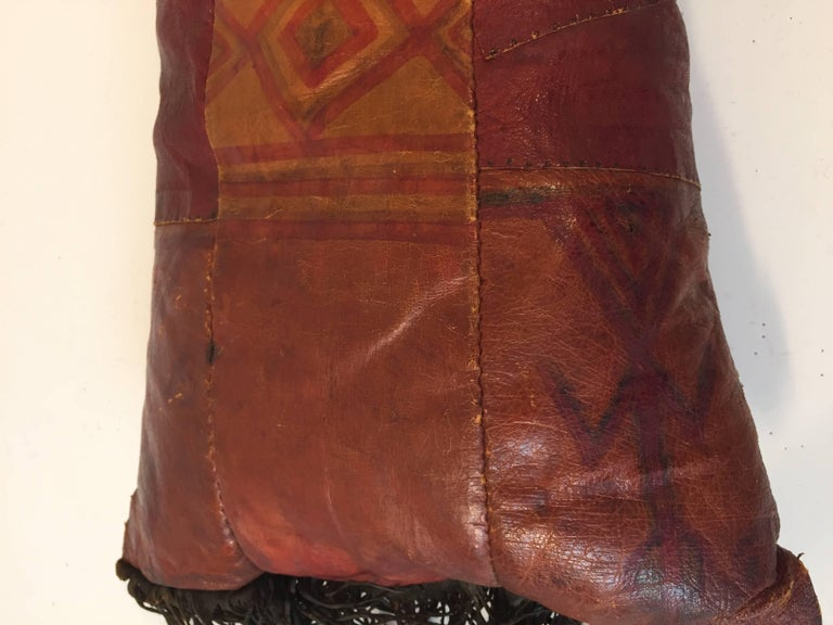 African Tuareg hand tooled leather pillow. Great colors, hand-painted with tribal geometric design with long leather fringes on each side. Handcrafted in Africa with pieces of leather sewn together and hand-painted, the back has a different