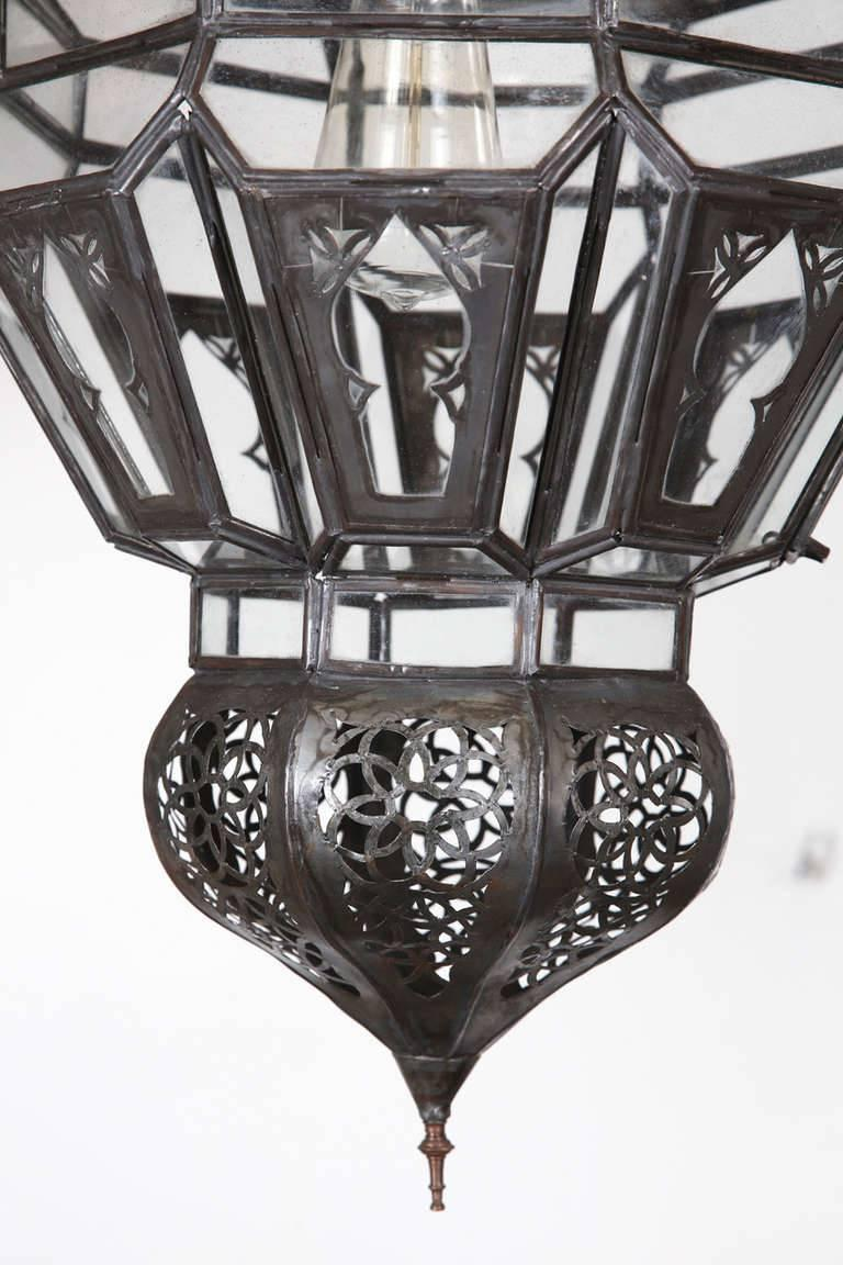 Moroccan Moorish clear glass with intricate metal filigree hanging chandelier. Delicately handcrafted by artisans in Morocco.  Bronze metal color finish.  Single light source one socket up to 60 watt max.  Comes with 3 feet chains and canopy, chains