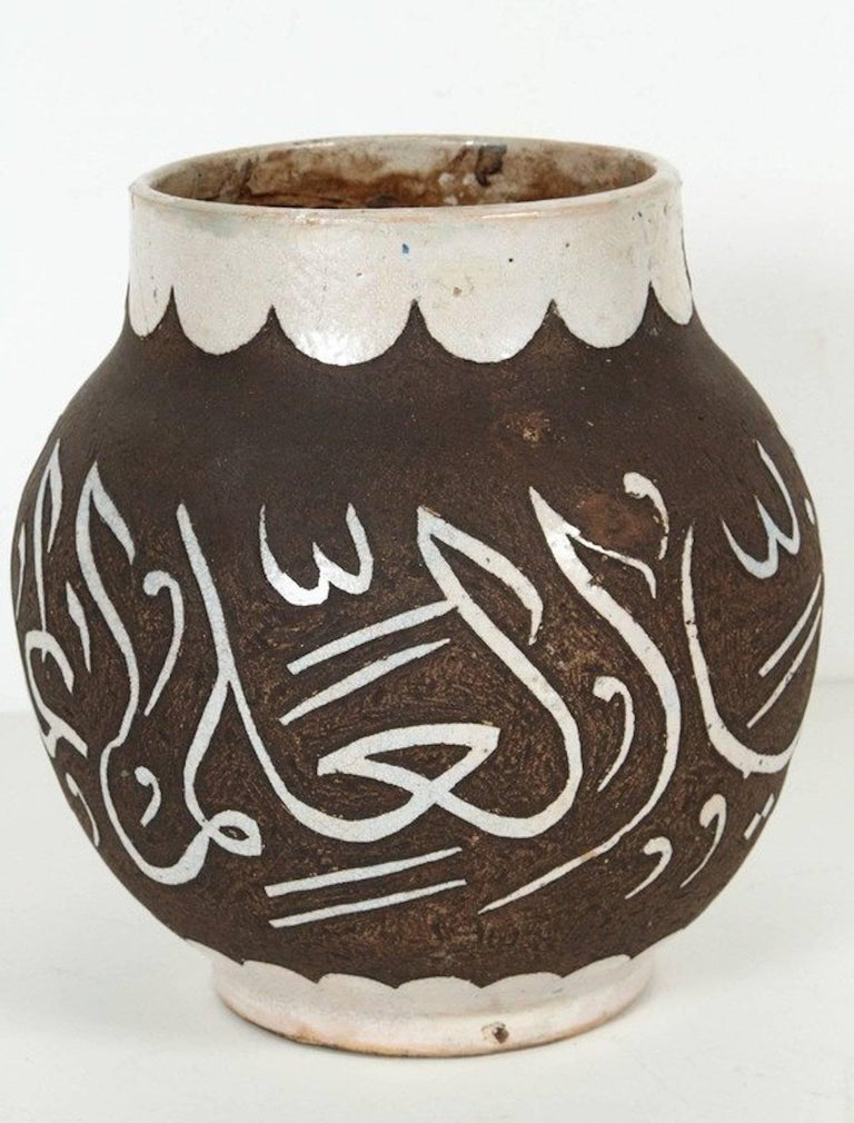 Decorative chiseled brown and ivory Moroccan ceramic vase from Fez hand-graved with ivory Arabic poetry calligraphy. Measure: Opening is 5.5in. A pair is available