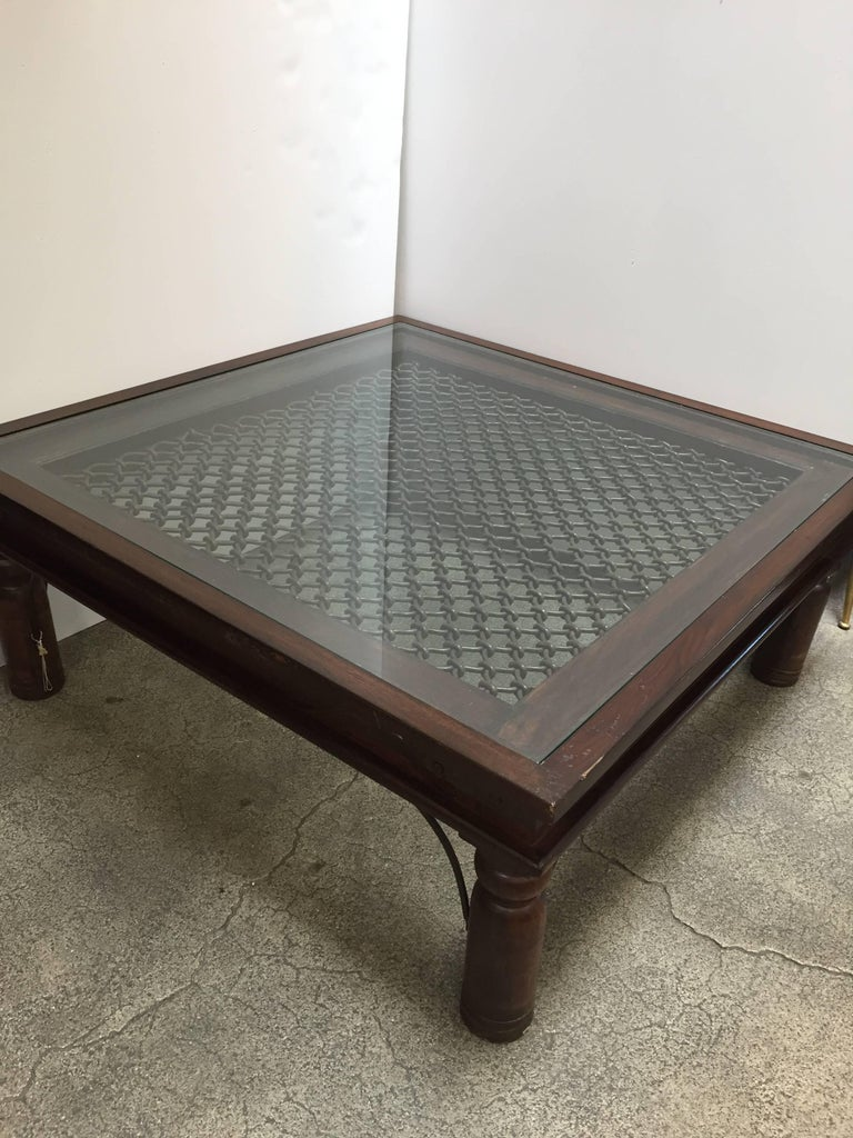 Anglo Indian style wooden coffee table with iron inset work and glass.  Large coffee table in solid teak wood with nailheads and metal accents support, very nicely carved legs, sides and corners are reinforced with metal iron pieces.  Spanish,