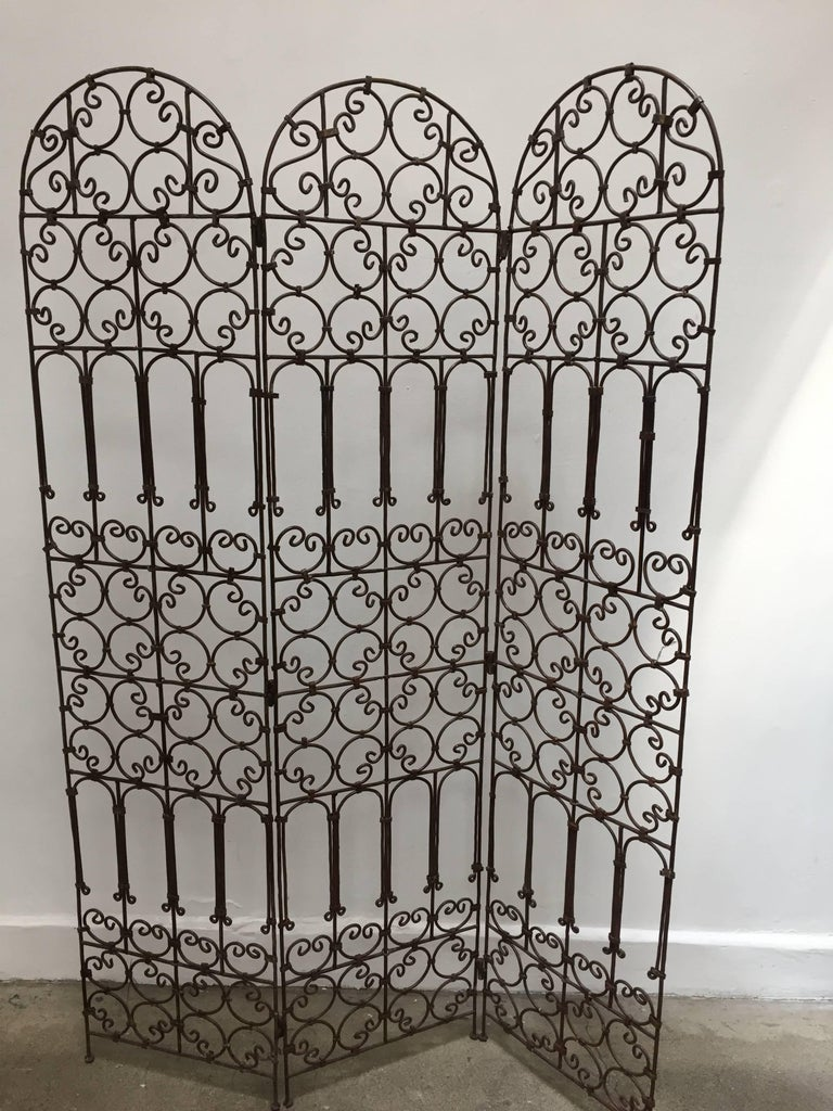 Hand-forged folding Moroccan screen with three panels decorated with Moorish designs.