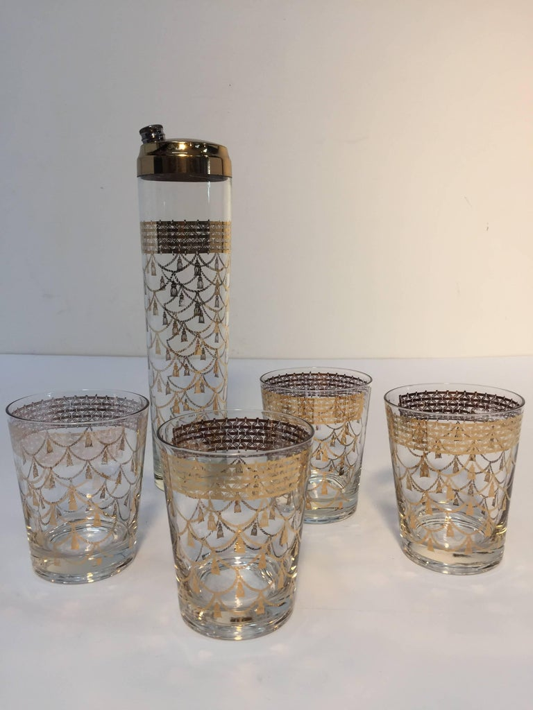 Elegant vintage Culver cocktail set of mid-century barware glasses with 22-karat gold leaf design. Includes four large cocktail glasses and one cocktail shaker with brass piece top.  Great design with gold tassels, and frieze in Hollywood regency