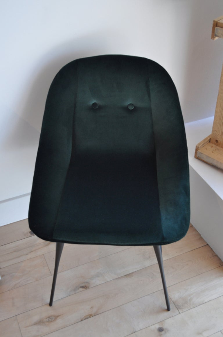 Green velvet upholstered dining chair with two button- tufted back detail on delicately sculpted bronze metal legs. Made to order and available in various standard fabric and leather upholstery options. Various metal finish options available for the