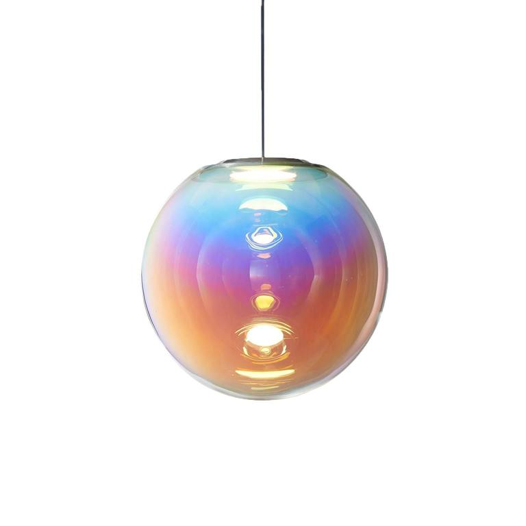The Iris pendant light appears like a permanent iridescent soap bubble. It is the result of ambitious craftsmanship and technological innovation. An OLED module provides both the light source and mount, with an iridescent film creating the