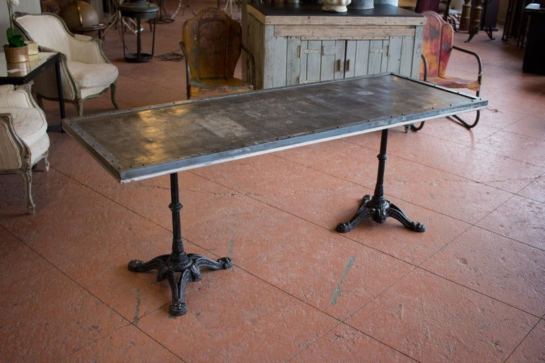 Vintage French garden table with double pedestal iron base and zinc riveted top as a garden table. Great patina.
