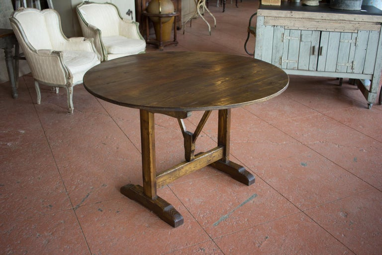 Vintage vendange tilt-top table. Originally these tables were used at a vineyard for testing and tasting the produced wine. It's a usable storable table that can be used inside or outside for al fresco dining.
