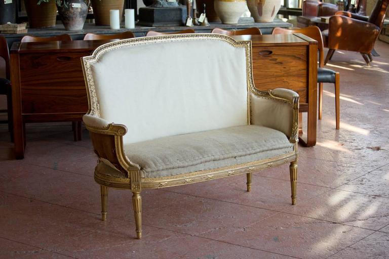 Antique Louis XVI petite bergère settee with original gilded frame.