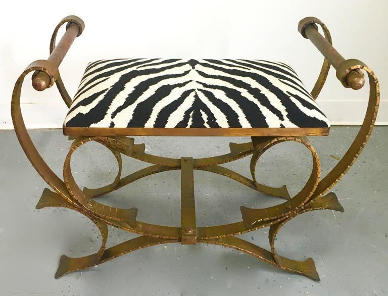 Early 20th century gilt classic wrought iron stool or bench upholstered in zebra print upholstery, the lines and attentive design definitely represent Hollywood in the early 1920s. Entire construction is hammered wrought iron, including the side